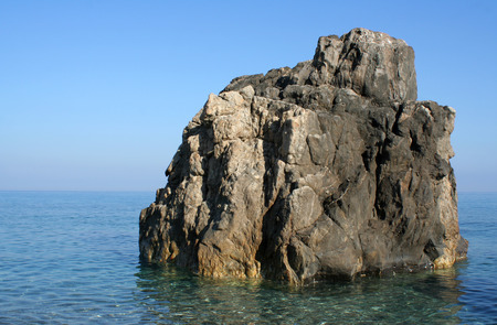 Big rock in the sea water next to the beach photo