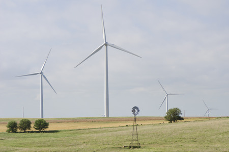 Massive wind turbines at a wind farm in the Flint Hills of Kansas harness the winds energy across the plains.  In the foreground is an example of the