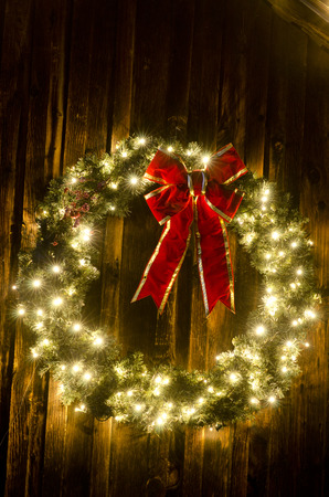 An old ranch barn is the perfect backdrop for a large lighted Christmas wreath, complete with red ribbon.  Photographed on a cold winter night, this wreath stands out against the weathered wooden background with plenty of copy space available for your own