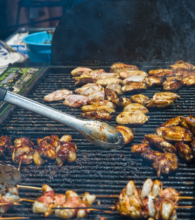 Smoke rises from a large grill covered with chicken kabobs, where food is prepared for festival patrons.  The chef is not in view, but his bar-b-que tongs are busy moving meat around.  Focus is on the middle ground, where tongs meet chicken, and there is