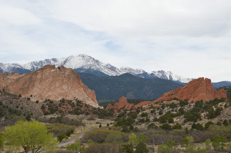 The beautiful sandstone rock formations of Garden of the Gods near Colorado Springs, Colorado stand out amongst the new leaves of Spring on surrounding trees.  The entrance to the public park is marked by mirrored flagstone signs and sets a nice introduct Stock Photo