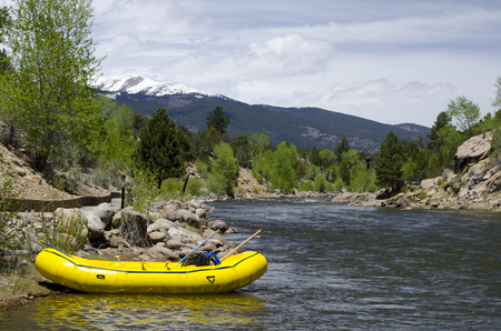 An yellow river raft sits empty on the side of the Arkansas River in Buena Vista, Colorado. After a year of heavy snows in the high country, the river runoff is high, and it appears that this group of rafters has taken time away from the whitewater to enj