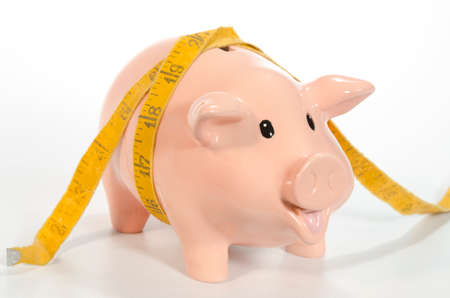 An empty piggy bank looks anxiously at the camera, hoping for its first deposit as a tape measure is wrapped around its body. The pig is photographed on a white background with plenty of copy space.  This image could be used to show how savings are squeez