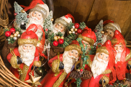 kris kringle: A basket full of santa ornaments is photographed on an angle.  Kris Kringle is wearing an ornate red coat with gold glittering trim and carrying a basket of berries and ornaments over his shoulder.  Some ornaments have a frosted Christmas tree and a star