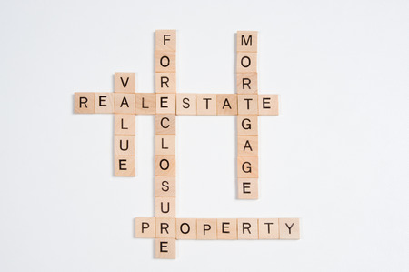 A crossword puzzle with answers regarding real estate values is photographed on a white background, providing plenty of copy space. Stock Photo