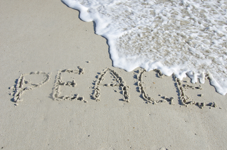 The surf of the ocean threatens to wipe away the word Peace, written in the sand with whitewater lapping on the beach.  There is plenty of copy space available for your own message. Stock Photo