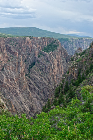 Storm clouds roll in over a large chasm carved by the Gunnison River.  Known as Black Canyon of the Gunnison National Park, the river cut through Precambrian rock over a billion years old. Here one can see metamorphic rocks like gneiss and schist, along w