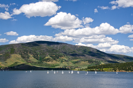A sailboat regatta on Lake Dillon in Frisco, Colorado is always an interesting sight.  The mountains behind, however, are still showing the results of a pine beetle infestation, killing thousands upon thousands of trees. Stock Photo