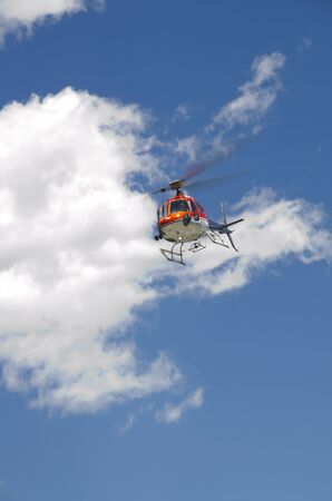 A helicopter hired for a scenic tour of the mountains gets closer to the ground as it comes in for a landing.