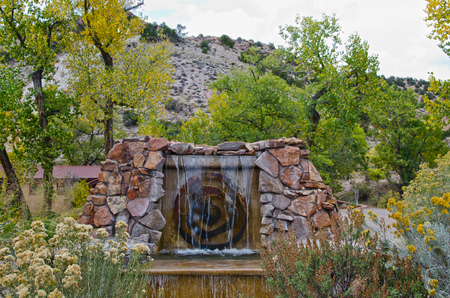The entrance to Ojo Caliente Hot Springs in New Mexico is marked by a sandstone fountain.  The resort stands between rugged hills and the river for which is is named. Stock Photo