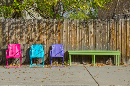 Three colorful lawn chairs sit empty against a wooden fence, with the Autumn leaves scattered among them. Zdjęcie Seryjne