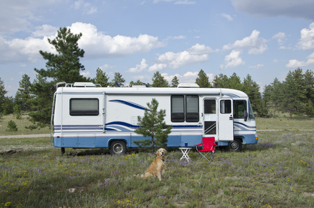 A Golden Retriever dog sits in front of his camper - a Class A motorhome. 版權商用圖片