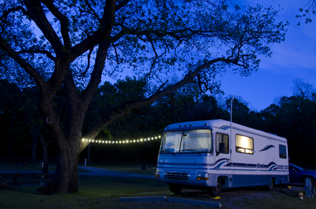A large motorhome sits under a huge pecan tree, lit up as night falls on the campsite.
