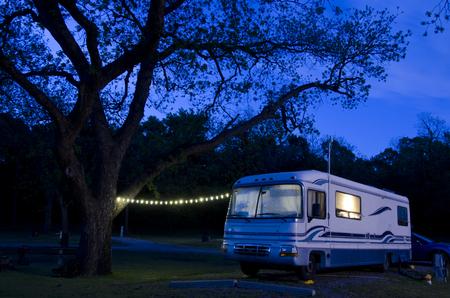 Ein großes Wohnmobil steht unter einem riesigen Pekannussbaum, der bei Einbruch der Dunkelheit auf dem Campingplatz beleuchtet wird.