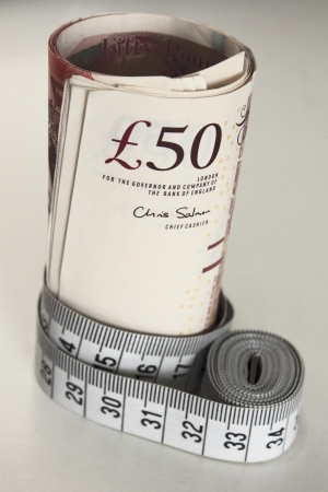 Fifty pound banknotes with tape measure on white background photo
