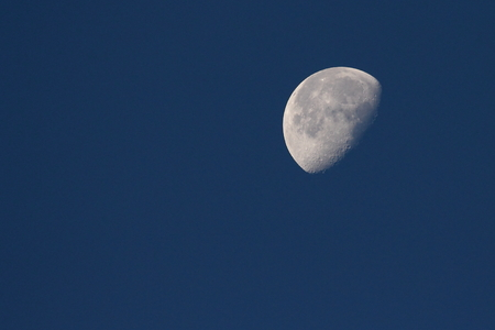 near side: Waning half moon on dark blue sky background Stock Photo