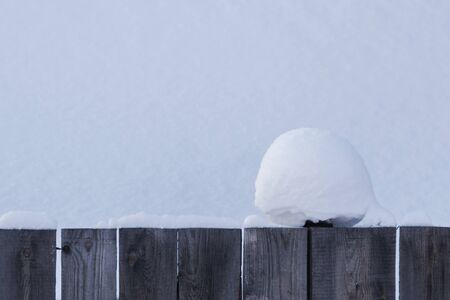 A beautiful clump of snow on a wooden fence with a snowy background. Christmas texture. Christmas texture.
