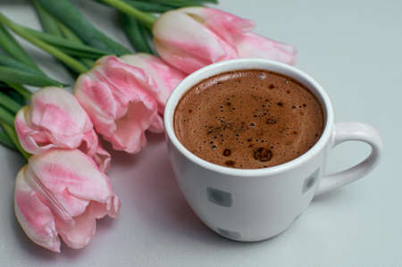 Tulips and cup of coffee on white background. Concept woman's or mother's day top view Imagens