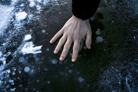 Frozen hand on cold ice