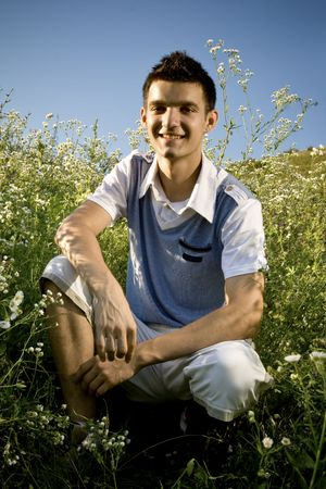 Boy among a field of daisies, with a clear blue sky as background and a peaceful atmosphere. photo