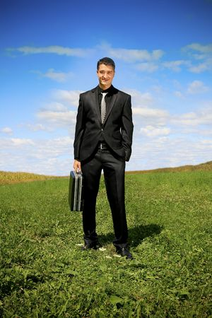 Young businessman outdoor holding a suitcase.