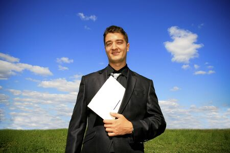 Young businessman outdoor holding a folder.