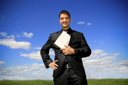 Young man in black suit in the middle of the field.