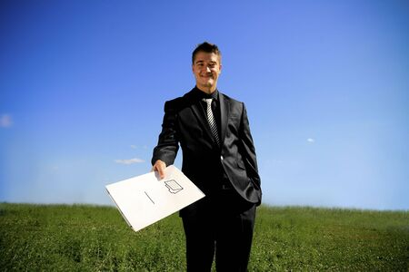 Business man in the middle of the field handing a folder