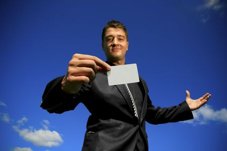 Slightly out of focus face of young man offering a focused card. Stock Photo