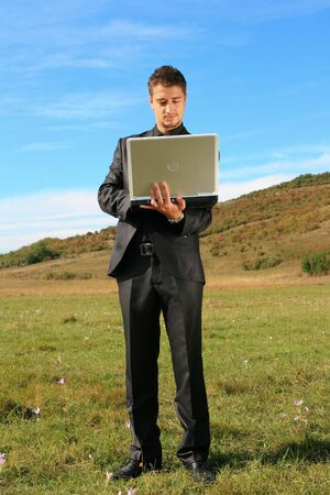 Standing person holding a laptop on a field. Stock Photo
