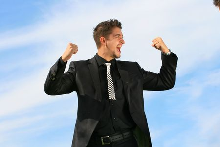 Ecstatic business man has his hands raised. Stock Photo