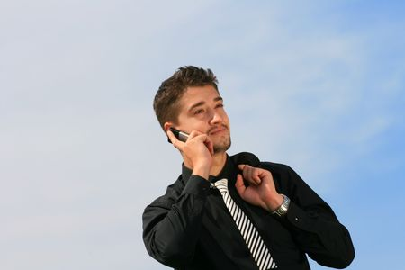 Young man holding suit while talking on the phone. Stock Photo