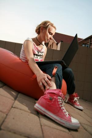 Girl looking at Laptop sitzen Standard-Bild - 3868144