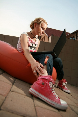 sneaker: Girl sitting down looking at laptop