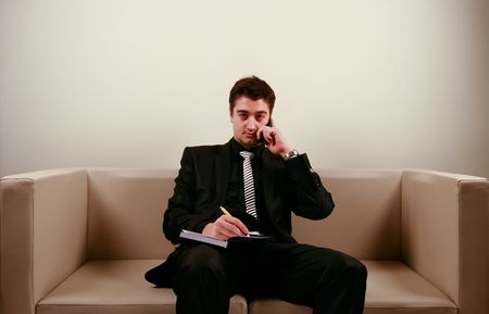 Taking notes while on the phone Stock Photo