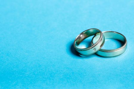 pair of wedding bands isolated on cyan background macro