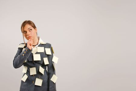 Business woman thinking trying to remember with her suit is full of stickers