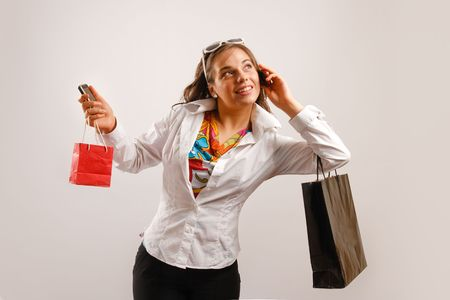 Modern looking young woman wearing white jacket talking on the phone and holding shopping bags