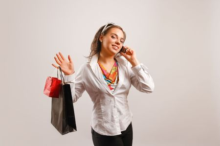 mobilephones: Modern looking young woman wearing white jacket talking on the phone and holding shopping bags