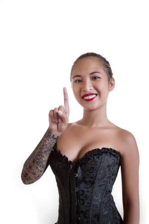 smiling girl with trigger finger pointing up, friendly girl with cool emotional expression series, big tattoo arm, cute face, corset fashion, cleavage