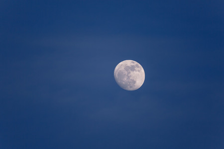 Full moon in daytime in blue hour with soft white clouds
