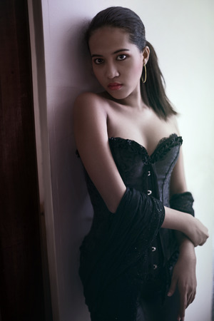 Model in corset lingerie looking at camera with sexy cleavage and golden earring 免版税图像 - 114781438