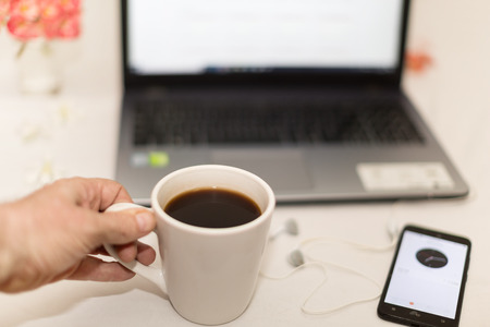 a table with white tablecloth on it a laptop cell phone, a mobile phone head set and a mug of black coffee in a hand a relaxing break time scene