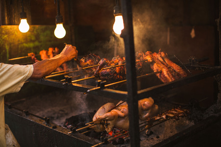 broiler spit roasted over tuxedo living coals in a simple electric illumination, the philippine lechon manok