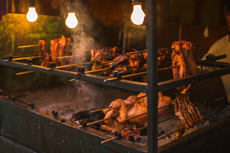outdoor street chicken barbeque grill with broiler spit roasted over tuxedo living coals at a simple electric illumination, the philippine lechon manok Stock Photo
