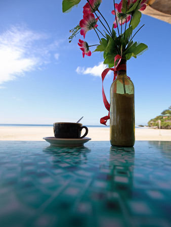 Bottle of coffee in a bottle and a vase bottle with sand reflection on a beach vacation scene
