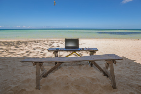 wood bench as desk in a idyllic beach with laptop notebook and mobile phone and mouse and eyeglas Stock fotó