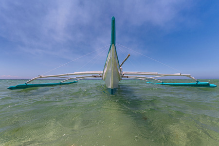 outrigger pumpboat on water in frontview with wide angle lens perspective with a blue sky white clouds background Stok Fotoğraf