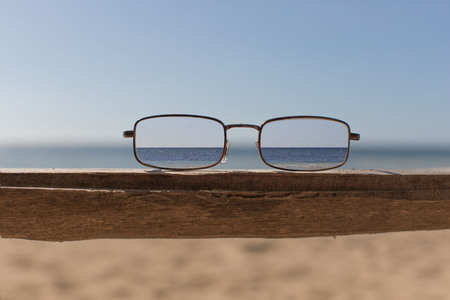 eyeglas on a board bench, defocused background focused  eyeglasses lens view, a beach with wite sand blue sea and blue sky