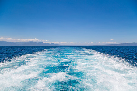 Wake water of a fast ferry speedboat with white foam, blue sky and deep blue sea on a sunny summer day